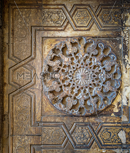 Round floral patterns framed by geometrical patterns carved into the exterior ancient stone wall of Sultan Hasan Mosque, Old Cairo, Egypt