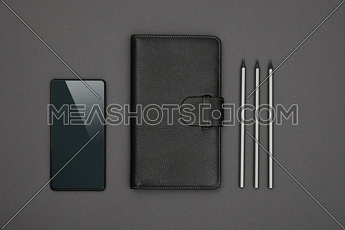 Close up one closed black leather cover notebook, pencils and smartphone over grey paper background, flat lay, directly above