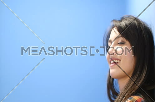 Seductive Woman Starring Into The Camera On A Blue Background