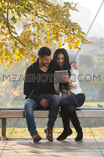 Beautiful Young Couple Sitting On Bench In The Park On A Beautiful Autumn Day - They Are Using Internet Via Digital Tablet