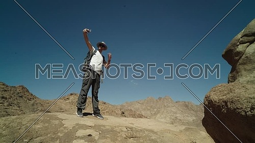 Long shot for a male tourist wearing a pink cap and travel backpack taking a selfie at Sinai Mountain for wadi Freij at day.