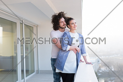 Couple in love sharing emotions and happiness while hugging on the balcony at home