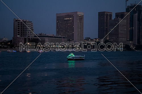 Long shot for the River Nile at Magic Hour showing buildings and motor boat