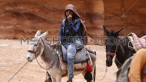 A young Bedouin riding a donkey in the city of Petra