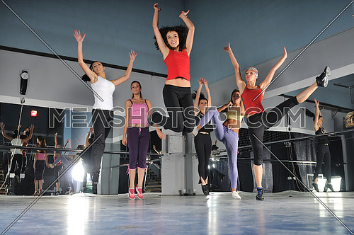 gorup of girls in fitness studio jumping in air