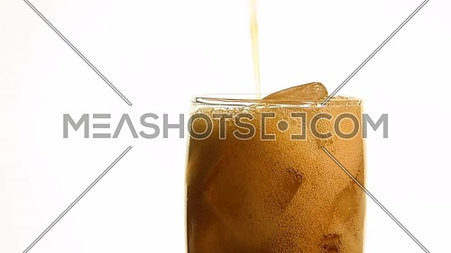 Extreme close up of pouring carbonated cola soft drink in transparent glass with ice cubes until full over white background, low angle side view