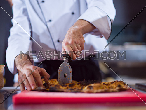 chef hands cutting baked bread out of the oven in a restaurant kitchen