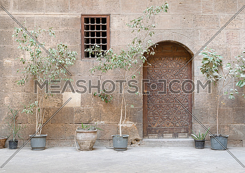 Facade of Zeinab Khatoun old historic house, with wooden ornate door and small window with wooden grid on stone wall, Medieval Cairo, Egypt
