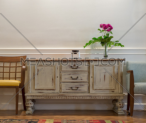 Studio shot of wooden vintage off white sideboard, glass vase with red flowers, two chairs on white wall and wooden parquet floor