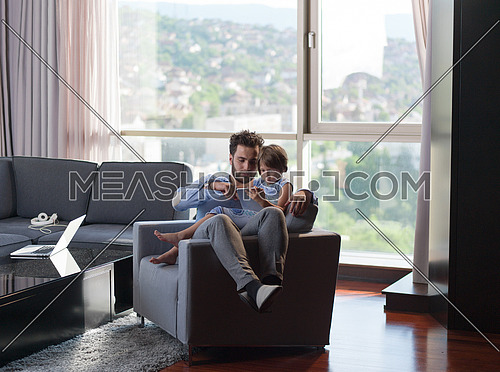little girl and her handsome father using a digital tablet and smiling, sitting on couch at home