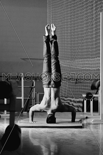 Young man performing  handstand in fitness studio. rear, back perspective.