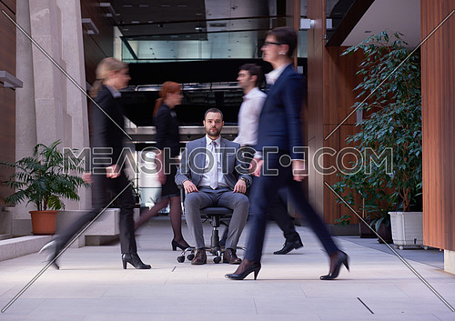 business man sitting in office chair,  people group  passing by: Concept of time, rush, organization