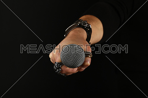 Close up man hand with metal rings and bracelet holding microphone over black background, side view