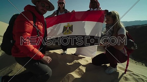 Follow out shot for group of tourists and bedouin guide spreading Egyptian flag while exploring Sinai Trail from Ain Hodouda at day.