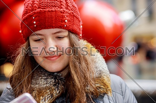 Outdoor portrait of beautiful young lovely girl using her mobile phone
