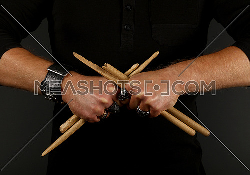 Close up man hands holding two broken crossed drumsticks over black background, front view