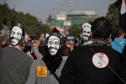 A group from their back wearing matyrs mask in a protest