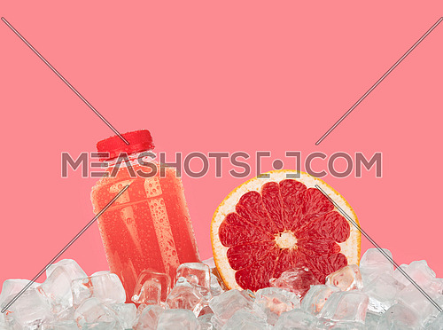 Close up one plastic PET bottle full of fresh pink grapefruit juice and cut half slice on ice cubes isolated on pink background, low angle side view