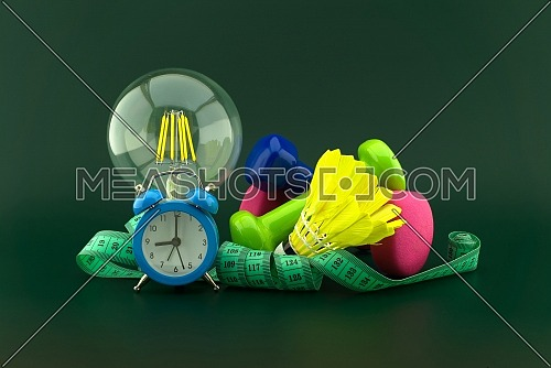 Starting healthy lifestyle idea concept with lamp light bulb, alarm clock and various sports inventory including dumbbells weights, shuttlecock and measuring tape over a dark green background