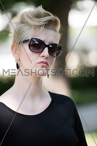 Beautiful fashionable young woman with short blond hair and sunglasses posing in the park