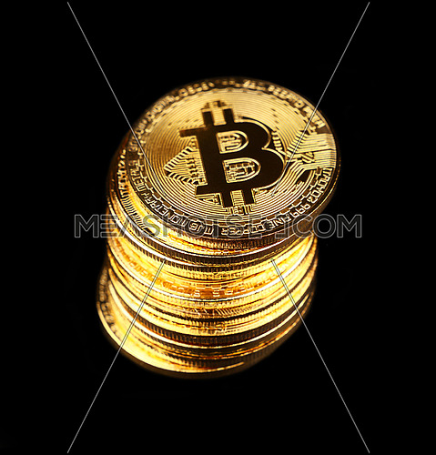Close up stack of golden bitcoin physical coins isolated on black background with copy space, low angle view, selective focus