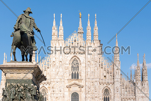 """Details of Duomo with the golden statue name """"Madonnina"""" on the top of the main spire and Vittorio Emanuale statue."""