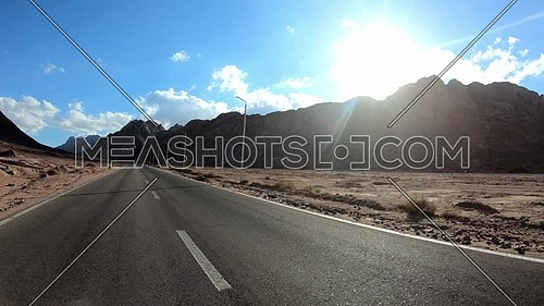 Follow shot for Sinai Mountain from a car driving on the route at day