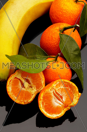 vivid orange tangerine and banana on black reflective surface