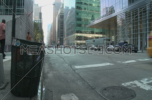 Long shot for New York City Showing Traffic, Cars and Trash can on corner  at day