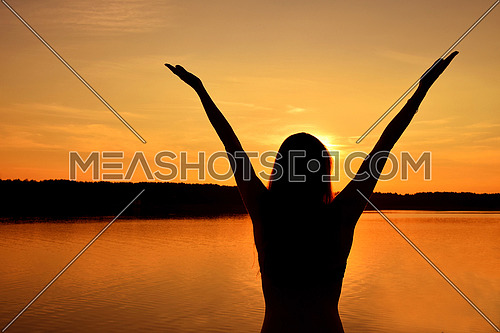 Dark silhouette of one young woman raising hands up over vivid orange sunset sky and lake water background, rear view