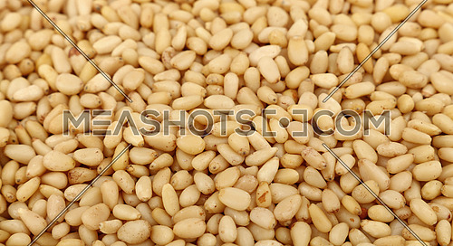 Whole white peeled pine nuts (cedar, pignolia, pinon) on retail market, close up, background, high angle view