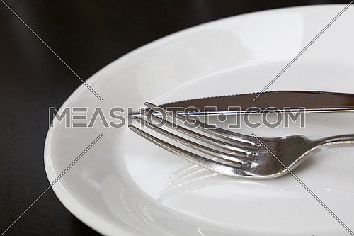 Metal fork and table knife utensils on white porcelain plate on black table, close up, low angle view