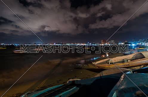 Track Left shot for sea shore showing fishing boats at alexandria at night