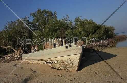 Long Shot for an Old wodden boat on the seashore with green tress in background at Wadi Lahmi at Day - 5D