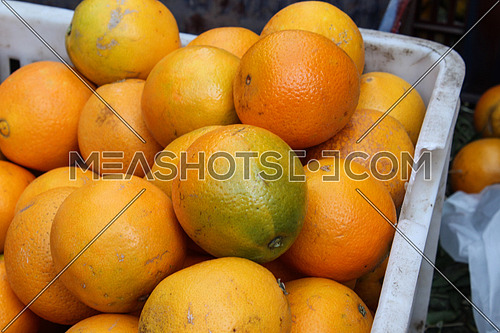 A basket of oranges, displayed for sale in a local food market