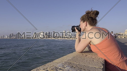 Right pan to a female tourist photographing Tel Aviv