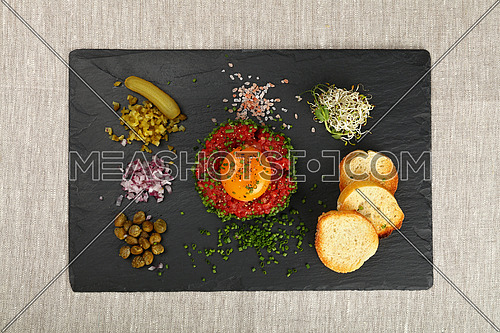 One portion of raw minced beef meat tartare steak with egg yolk, green chive, onions, cucumbers, capers, salt and toasts at black slate board on table, close up, elevated top view, directly above