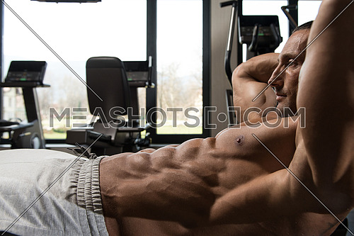 Muscular Mature Man Exercising Abdominals On Exercise Ball In Modern Fitness Center