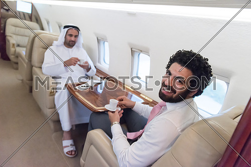 Young middle eastern successful businessmen enjoyed by talking with Arab business partner while sitting in private jet