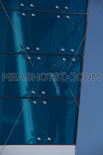 Outdoor shoot of a senior executive talking on the phone through glass front of a  corporate building with blue sky at the background
