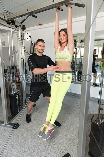Personal Trainer Showing Young Woman How To Train On Abs Abdominals In The Gym