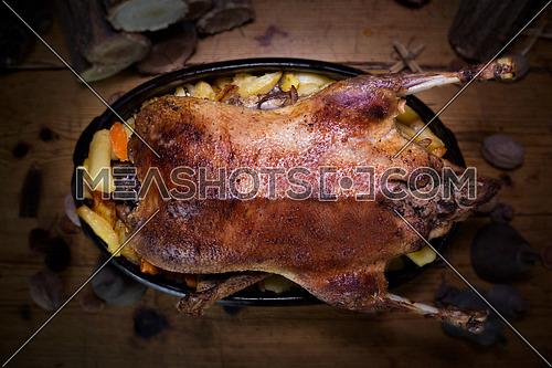 Christmas Duck Roast At The Wooden Table With Wood Logs and Pine Branches In The Background