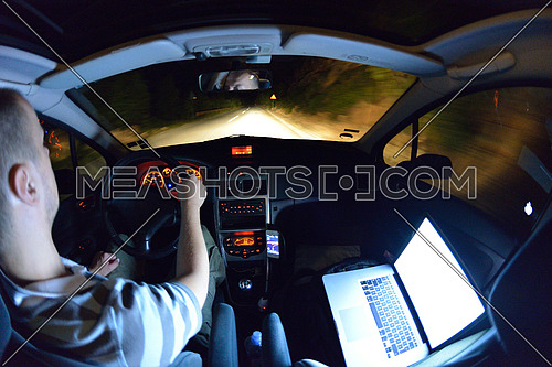 man working on laptop while drivig car on night and navigating with smart phone