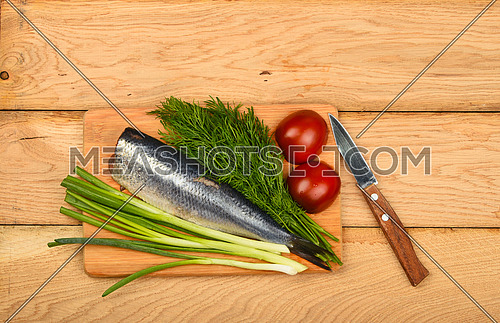 Herring double fillet with onion, dill and tomatoes on bamboo board win small knife on vintage wooden table surface
