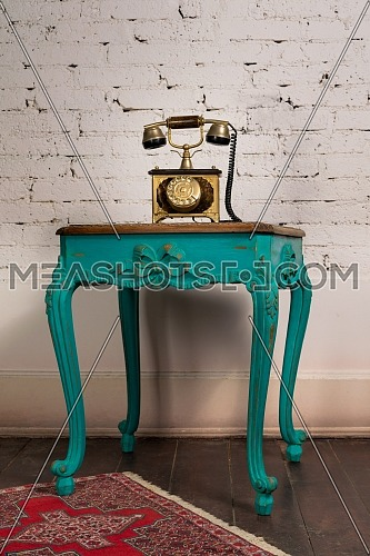 Retro composition of green vintage wooden table and old golden telephone set on a background of red carpet, dark brown wooden floor and white bricks wall
