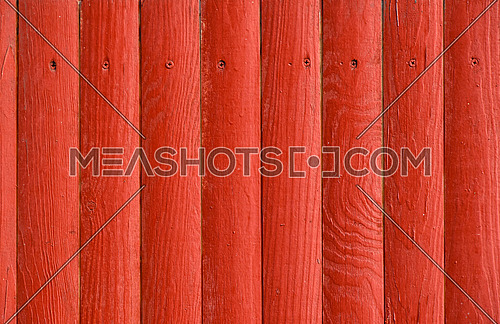 Red vintage grunge aged painted wooden panel with vertical planks and screw heads texture background