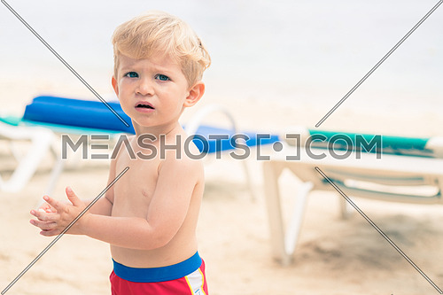 Beautiful serious infant  boy on the beach,used split toning for vintage style.