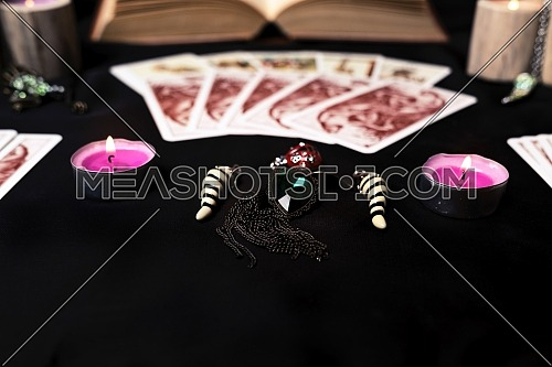 Candles and old tarot cards on black silk. Halloween and fortune telling concept. Mystic background with occult and magic objects on witch table.