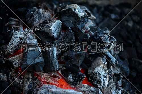 Coal in a black metal grill catching fire