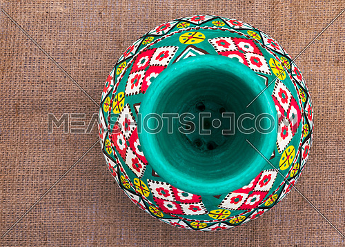 Top view of a green Egyptian handcrafted artistic pottery jar on a sackcloth background